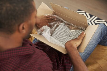 Man Sitting On Sofa At Home Opening Online Clothing Purchase