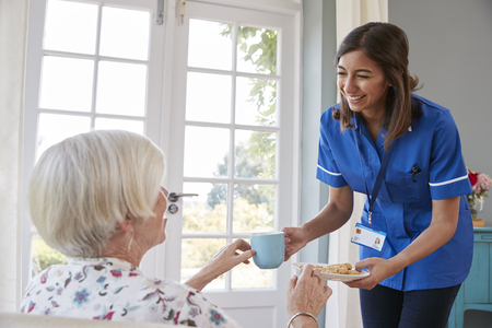 Nurse serving tea to senior woman at home, close up Stock Photo