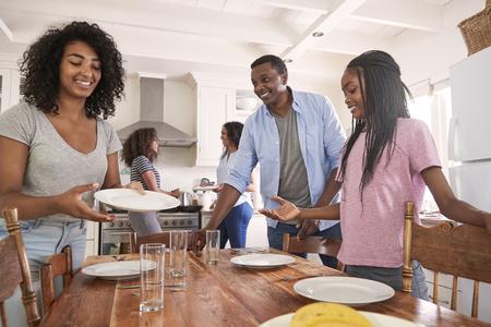Familie met tienerdochters die lijst voor maaltijd in keuken leggen Stockfoto