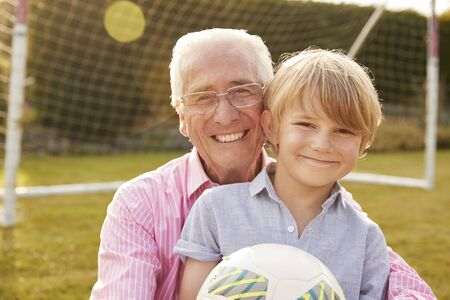 Senior man and grandson holding ball smiling at camera