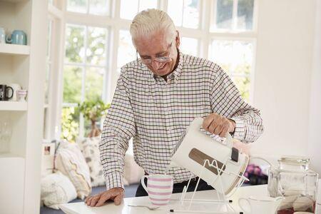 Senior man making cup of tea at home