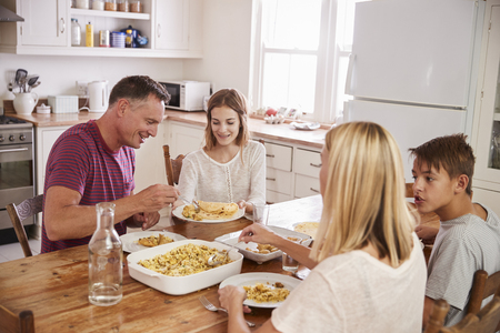 Family With Teenage Children Eating Meal In Kitchen Foto de archivo