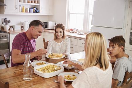 Familie met tienerkinderen die maaltijd in keuken eten