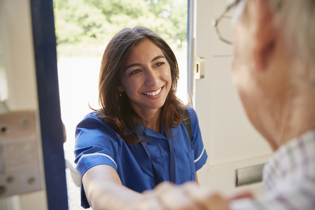 Nurse on home visit greeting senior man, over shoulder view Stock Photo