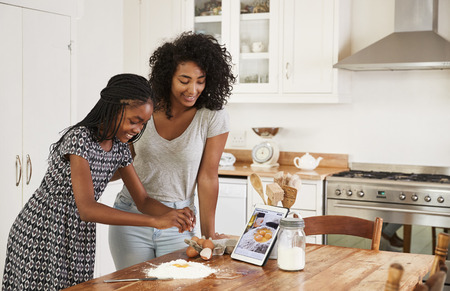 デジタル タブレットのレシピに従う十代の女の子