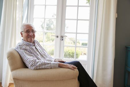 Senior man sitting in an armchair turns smiling to camera