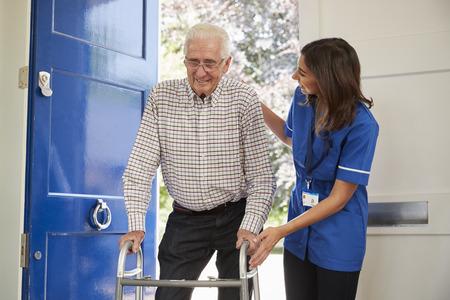 집에서 도보 프레임을 사용하여 수석 남자가 간호사 도움이됩니다.