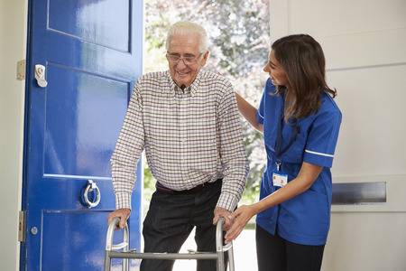 Nurse helps senior man using walking frame at home, close up