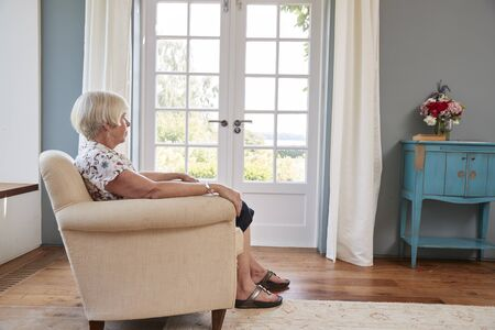 Senior woman sitting alone in an armchair at home Stock Photo