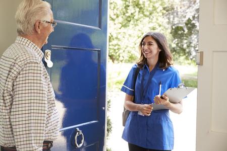 Hogere man die vrouwelijke verpleegster begroeten die huisbezoek maakt