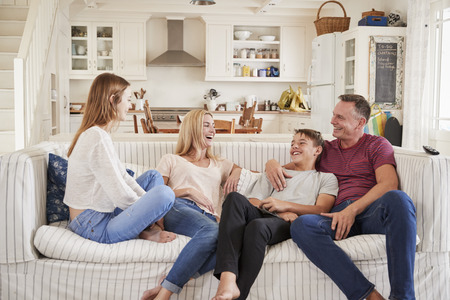 Family With Teenage Children Relaxing On Sofa Together Stock Photo