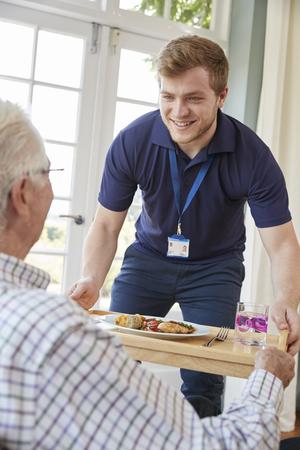 男性介護福祉士が自宅で年配の男性にディナー