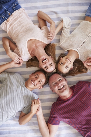 Overhead View Of Family With Teenage Children Lying On Bed Stock Photo