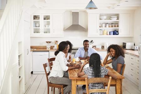 キッチンで朝食を食べて、10 代の子供連れのご家族