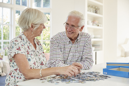 Senior couple doing a jigsaw puzzle at home Stock Photo