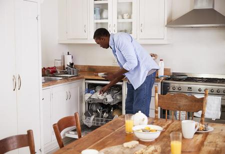 Man Clearing Breakfast Table And Loading Dishwasher Zdjęcie Seryjne - 88062146