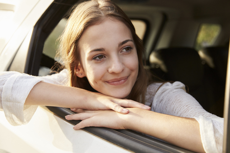 Teenage Girl Looking Out Of Car Window On Family Road Trip Stock Photo
