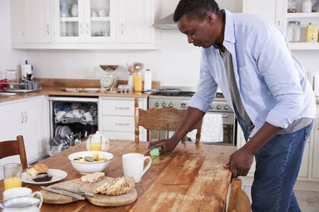 Man Clearing Breakfast Table And Loading Dishwasher Zdjęcie Seryjne - 88062152