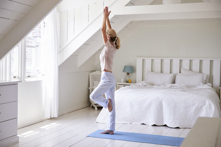 Woman At Home Starting Morning With Yoga Exercises In Bedroom Reklamní fotografie
