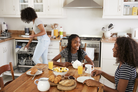 Three Teenage Girls Clearing Table After Family Breakfast