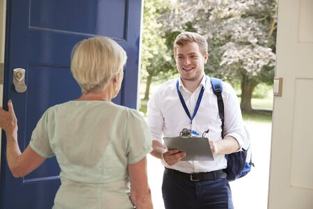 Senior woman opens door to male charity worker doing survey
