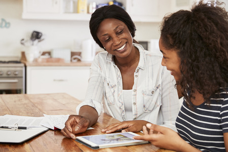 어머니는 십대 딸과 함께 디지털 태블릿을 사용하여 숙제를 도와줍니다.