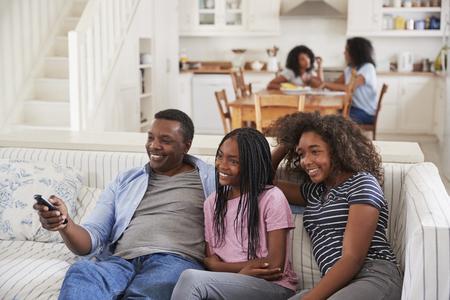 10 代の娘とテレビを見ながらソファに座っている父