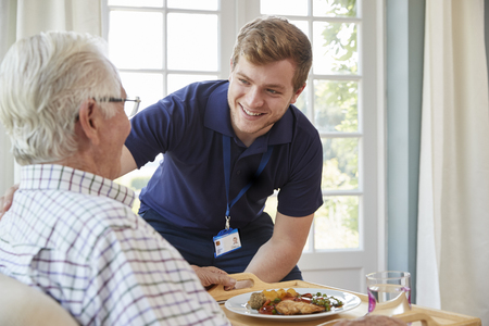 Male care worker serving dinner to a senior man at his home Stock Photo - 88062501