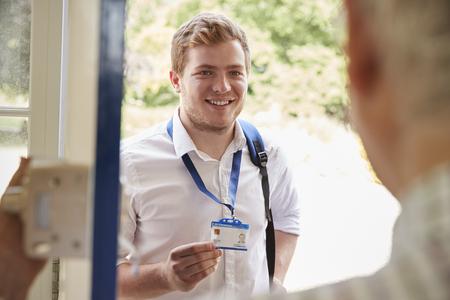 彼の正面玄関で年配の男性に ID を示す男性介護福祉士