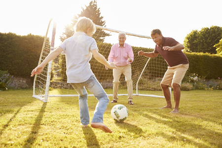 Three male generations of a family playing football Banco de Imagens