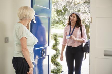 Senior woman opens door to female care worker showing her ID Standard-Bild