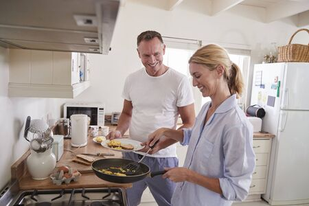Mature Couple Chat In Kitchen As Woman Prepares Breakfast Banco de Imagens - 88062560
