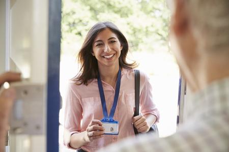 Hogere man die voordeur opent aan jonge vrouw die identiteitskaart toont Stockfoto
