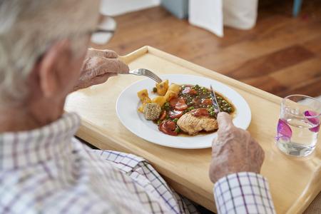 Over shoulder view of senior man eating dinner at home Stock fotó