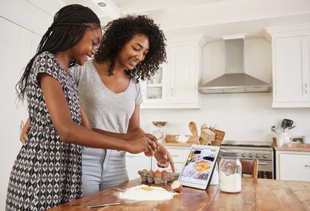 디지털 태블릿에서 조리법을 따르는 십대 소녀들