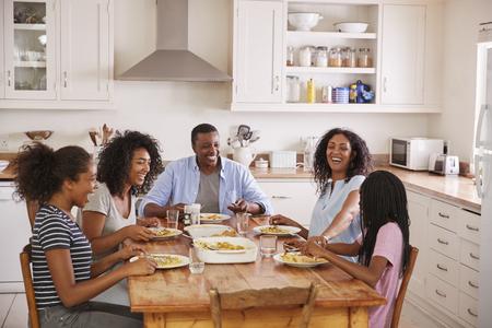 Familie met Tienerkinderen die Maaltijd in Keuken eten Stockfoto