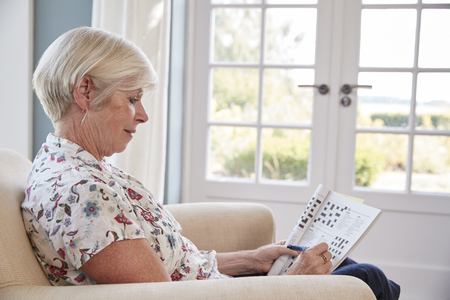 Senior woman sitting in armchair doing  a crossword at home