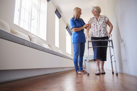 Nurse helping senior woman use a walking frame, full length Фото со стока