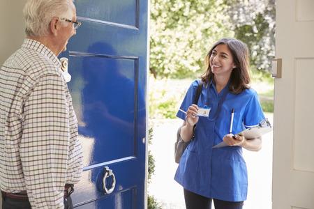 Female nurse showing ID to senior man at his front door Stock fotó