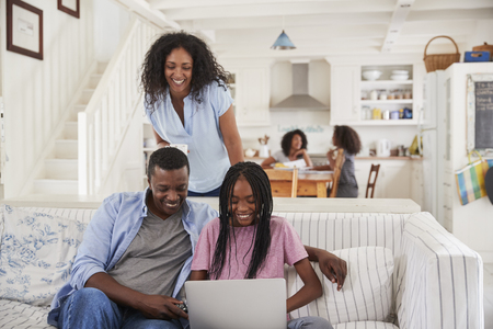 ノート パソコンをソファーに座っていた 10 代の娘を持つ家族 写真素材