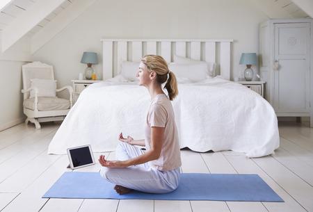 寝室で瞑想アプリを使用してデジタル タブレットを持つ女性 写真素材