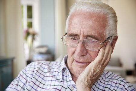 自宅で考えて心配している年配の男性をクローズ アップ 写真素材