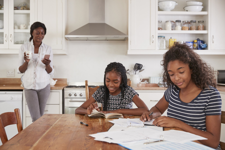 Mother Uses Phone As Daughters Sit At Table Doing Homework