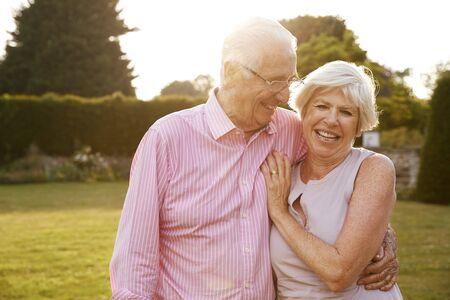 Senior couple in garden smiling to camera, close up