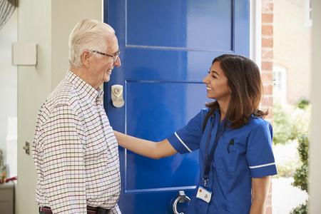 Nurse on home visit greeting senior man at his front door Standard-Bild