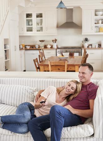 Couple assis sur le canapé à regarder la télévision ensemble Banque d'images - 88062811