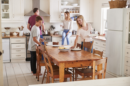 Family With Teenage Children Laying Table For Meal In Kitchen