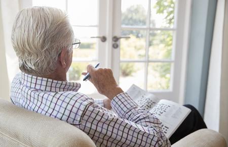 やってクロスワード、肘掛け椅子に座っている年配の男性をクローズ アップ