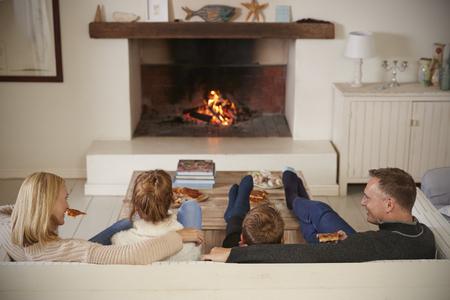 Famiglia seduta sul divano in salotto accanto al fuoco aperto