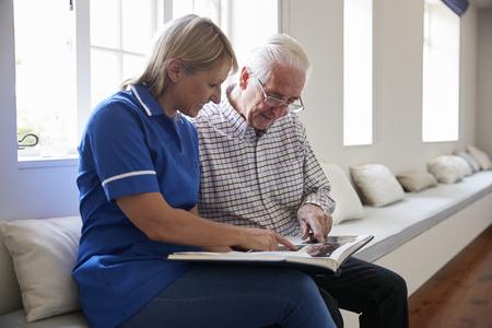 Hogere mensenzitting die fotoalbum met zorgverpleegster bekijkt
